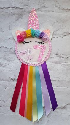 RAINBOW UNICORN PARTY BIRTHDAY ROSETTE BADGE Handmade Unicorn birthday rosette personalised with name and age. The top has unicorn sleepy eyes with eyelashes, ears, horns and cute mini felt roses. The bottom is trimmed with pretty ribbons to match the felt roses in rainbow colours. The