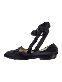 Black Chanel satin ballet flats with bow accents at uppers and tie closures at ankle straps.