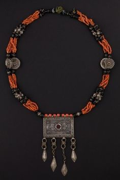 The big Necklace is made with silver flat beads and are decorated by a fine granulation, by filigree which intersect the Mediterranean coral. The central rectangular pendent that is decorated by glass paste, is an amulet container.        Origin: Tagikis
