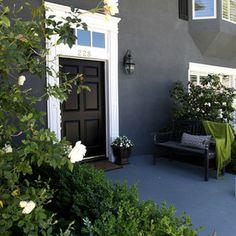 Black door, white trim, green plants