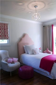 Chic girl's bedroom design with pink headboard, hot pink throw, white hotel bedding with pink stitching, West African pink hamper basket, white Moroccan nightstand and gray window panels curtains.