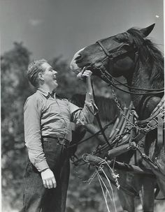 """Original, vintage photo of Nelson Eddy by MGM photographer, Eric Carpenter. Back of the photo states: """"NELSON EDDY TURNS FARM HAND...In between studio calls for his current co-starring role with Jeanette MacDonald in Metro-goldwyn-Mayer's 'Sweethearts', the musical star can be found on his valley ranch pitching hay, driving his team and acting as general chore-boy."""" - ESCANO COLLECTION"""