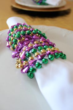 Use mardi gras beads as simple and inexpensive napkin holders for a Mardi Gras dinner.