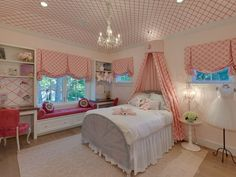 Adorable girl's bedroom with hot pink Moroccan tile wallpapered tray ceiling illuminated with a white crystal chandelier over a beige geometric rug anchoring the gray half moon bed with headboard and footboard dressed in white bed linens accented with a pink monogrammed bed canopy paired with pink curtains as well as matching swagged roman shades dressing the windows.