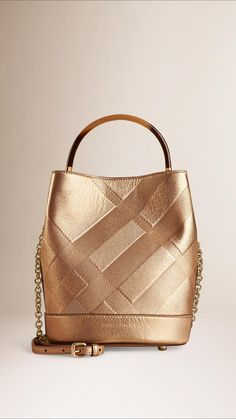 Burberry's small bucket bag In embossed check leather is the metallic accessory we all want this Spring.