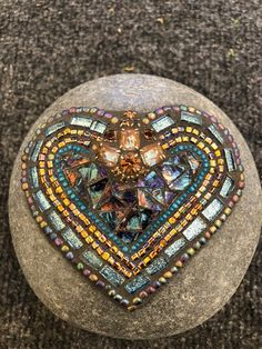 The colors on this mosaic Heart are really well balanced with both sparkles and muted colors. The centerpiece is a vintage glass piece and the center is a multi colored Van Gogh glass. The rock measures about very stunning Mosaic Rocks, Mosaic Stepping Stones, Pebble Mosaic, Stone Mosaic, Mosaic Glass, Mosaic Flower Pots, Mosaic Garden, Landscaping With Rocks, Backyard Landscaping