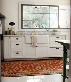 Steel framed window, brass faucet, farmhouse sink, marble countertops, and a kilim rug...so many good things in this kitchen.
