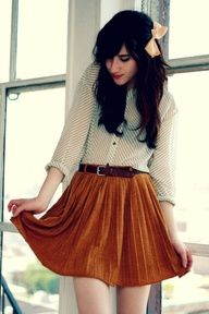 Sheer white blouse tucked into belted high-waisted circle skirt.