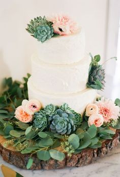 Three-tiered wedding cake with ranunculus, anemones, and succulents, The Butter End.  See more bohemian wedding cakes.