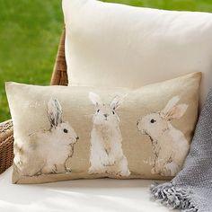 three rabbits on a pillow