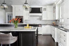 Monochrome French hood stands boldly amongst white shaker cabinets, white brick backsplash tiles, and nickel knobs and vintage pulls.