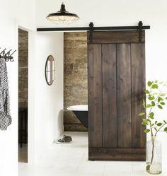une salle de bains rustique équipée avec une baignoire, une porte de grange coulissante en bois foncé