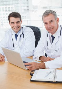 Doctors posing while working together on laptop in bright office ...  20s, 50s, Looking At Camera, agenda, caucasian, clinic, colleagues, computer, confident, desk, diary, doctor, happy, healthcare, hospital, indoors, lab coat, laptop, male, man, mature adult, medical, meeting, notebook, office, pen, portrait, practitioner, profession, professional, sitting, smiling, specialist, staff, stethoscope, team, technology, using, wireless, young adult