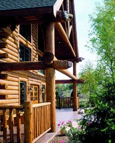 Extend porch roof and use logs on upper deck with stone piers for base of porch.