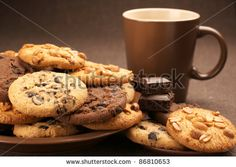 Assorted cookies in brown plate and brown mug of coffee on brown canvas. - stock photo