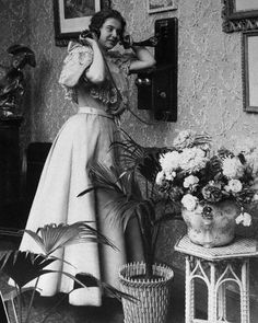 Woman Talking on Wall Mounted Telephone, ca 1890.