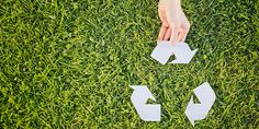Hand making complete a recycling symbol over green grass - top view with copy…