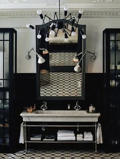 Black and white bathroom, black chandelier, black framed mirror, vintage trough stone sink | Remodelista