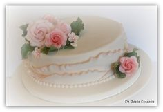 A small wedding cake with ruffles and roses