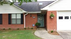 Red brick house with black shutters and front door painted with BEHR Plus Venus Teal.