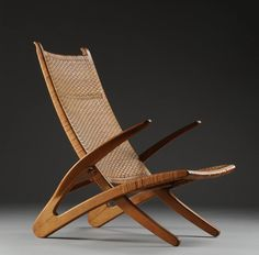 The folding 'Dolphin chair' (model JH510) designed by Hans Wegner. Originally designed as outdoor seating is framed in oak with cane seat and back First produced by cabinetmaker Johannes Hansen in 1950. Photo: lauritz