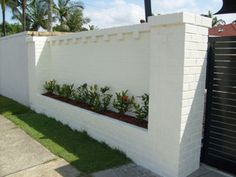 Here's a white brick fence with built in landscaping.