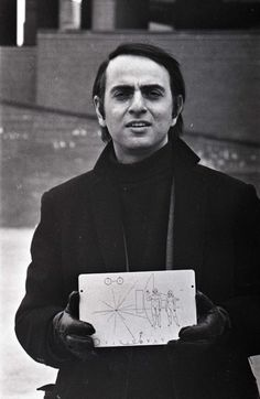 Carl Sagan, holding a copy of the plaque that flew with the Pioneer space probes, in Boston, March 1972. Photo by Jeff Albertson. (University of Massachusetts)