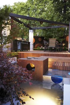 This modern deck looks awesome with the lighting and surrounding garden!