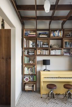 One of the family's favorite rooms in the house is the library. Young's wife is an avid reader and founded a children's literacy nonprofit here in Orlando. The couple needed a space for everyone's books, and finding a place where they could display them side-by-side was important. The bookshelf, part of a larger shelving grid, is built around a bright yellow piano. Photo 14 of 1600 Lakeside modern home