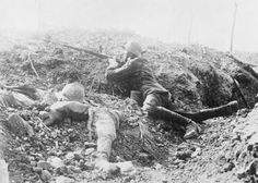 Battle of Verdun, A German soldier aims his rifle from a shallow fold in the ground near Fort Vaux with a partially buried dead French soldier on his left. German Soldier, German Army, World War One, First World, Bataille De Verdun, Ww1 Photos, Ww1 Pictures, Photographs, Kaiser Wilhelm