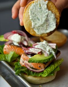 Salmon Sliders with Avocado // topped with a yummy yogurt, cucumber + dill sauce [eliminate bun for low carb] #protein #healthy