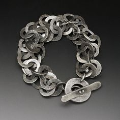 This stunning bracelet is meticulously hand fabricated from sterling silver. Each link is formed, soldered , hammered and oxidised. The hand