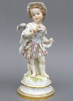Meissen Model: L 111        Description: Cupid as Coquette   Modeled By: Heinrich Schwabe ca.1878   Mark: L 111       Painter Number: 47 - Gerstmann & Klemm    Height: 8.8 in - 22.4 cm  Notes: Blue Wings