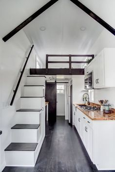 The queen bedroom loft is accessed by a storage staircase next to the kitchen. Below the staircase is a bar height table.
