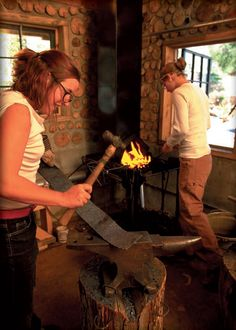 Lady blacksmiths forming metal