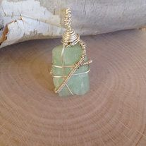 """Raw Aquamarine Wire Wrapped Pendant. Sterling silver wire. Small and pretty stone. Measures 1"""" long, and 0.75"""" wide. Perfect for a short necklace or keychain.  Aquamarine is the Stone of Soothing. It encourages compassion and tolerance, suppresses anger and hostility, and releases and cleanses ..."""