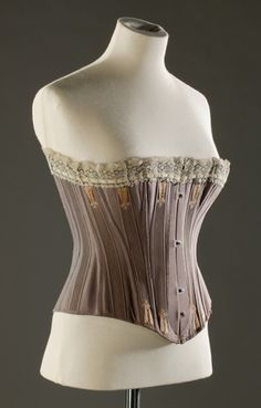 """Spoon Busk Corset: 1880-1885, sateen cotton, twill cotton, embroidery, lace, silk, whalebone. """"A corset cost anything between 12 shillings and 6 pence (65 pence) and 21 shillings (1.05 [pounds]) at this date. The mechanisation of the corset-making trade (with sewing machines in factories rather than staymakers in workshops) meant that more corsets were available at lower prices to more women."""""""