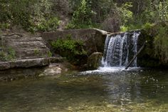 A view of the waterfall and natural steps beside it at St. Edwards Park.  Hike along Bull Creek.  Water seeps from moss-carpeted limestone bluffs with a myriad of ravines and gullies  The park abuts a tract of the Balcones Canyonlands Preserve.