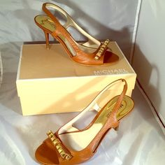 """Michael Kors Livvy Sandal in Luggage leather Open-toe slingback sandals in Luggage Brown leather.  Leather lining and insole.  Size 6 1/2 M.  3 1/4"""" heel.  Bow embellishment decorated with gold pyramid studs.  Stacked heels.  Great shoe for everything from jeans to a night out.  Left heel has small hole in leather wrap.  Otherwise, excellent condition.  Original box is included. Michael Kors Shoes Heels"""