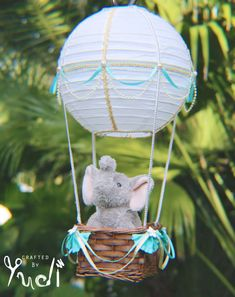 This exquisite decorative hot air balloon paper lantern has been handcrafted with soft teal ribbons and pearl accents making it a unique and beautiful addition to any childs room or baby nursery. The basket, made from natural fibers and adorned with mini white ribbon flowers and soft ribbon scalloped embellishments, can hold a small plush toy (less than 1lb). The 10 white lantern, adorned with pearls and light blue ribbon and embellished with gold glitter ribbon, makes this hot air balloon…