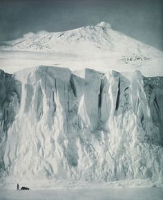 """""""THE RAMPARTS OF MOUNT EREBUS"""" — On Antarctica's Ross Island in 1911, photographer Herbert Ponting captured this stunning photo of a cliff on Barne Glacier with volcano Mount Erebus behind. Erebus last erupted in 2008.  (Royal Collection Trust)"""