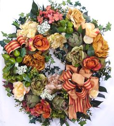 """This beautiful Spring, Summer flower door wreath sets on a nature grapevine wreath base.  The wreath is embellished with lots of greenery, beautiful beige and tan Peony, orange/olive green Roses and Hydrangea, beige/green Peony. The wreath is accented with three Artichokes and three clusters of small green Pears. I finish the wreath with two orange/tan  ribbon bows .   The wreath measures from tip to tip at 28"""" (L) x 27"""" (W) x 7.5""""(D)."""