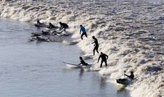 Surfers ride the wave of the tidal Severn bore on the River Severn at Newnham, England, on March 21, 2015. @Geoff Caddick/AFP/Getty Images | www.godsfolder.com #GodsFolder