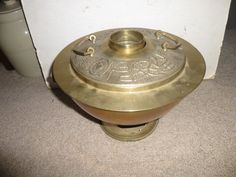 This classic Asian (I am guessing Korean, but possibly Chinese) Brass Brazier was a great way to heat a small room or yurt - fill the ring with water and place coals in the lower chamber - the heat from the coals evaporates the water putting moisture into the cold dry air and the steam wafts prayers to the totem animals on the lid. Fun and functional form great for storage and display.  Measures: 10 high x 11 diameter - stove / oven door is 2.5 wide by 1.5 high - 2.3 diameter chimney stands…