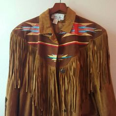 """Vintage Southwest 100% Suede Leather Navajo Coat New!  Dead old stock. Mint! Immaculate! Never worn. Rich Brown 100% Suede leather jacket with gorgeous fringe,  Navaho embroidery throughout, Indian head nickel buttons. Boho, cowgirl, western chic, ethnic Indian design. Size small but not a tailored fit. Many size mediums could wear this. 19"""" flat from shoulder to shoulder seam, 20"""" flat coat width, 37"""" flat length to bottom of fringe. Approximate measurements. This amazing coat is a jewel…"""