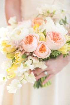 Peach Garden Roses with yellow Tulips and white Sweet Peas.