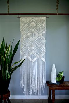 SHOP NOTICE: I am due to have my first baby in the first week of December! I will likely temporarily close my shop during that time, so get those holiday orders in soon! This large macrame wall hanging was made from 3mm natural white cotton rope and hangs from a hand stained wooden dowel. Features a geometric diamond pattern. A unique piece that is sure to add texture and interest to any room! Would make an amazing gift! Wooden dowel is 24, macrame measures approx. 20 wide by 64 long…