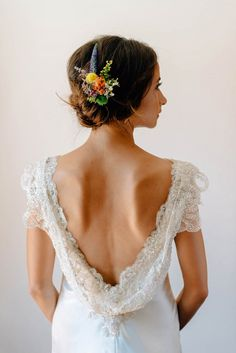 This cowl-back wedding dress and that wildflower hairpiece - we're obsessed! Photo by Mathias Fast