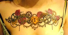 A steampunk tattoo on a girls chest of a mechanical heart with a keyhole surrounded by roses, cogs and pearls. The locket, clockwork mechanisms and strings of pearls shown in the tattoo are objects that define women of the Victorian era and are often used in steampunk tattoos.