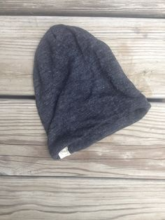 Reversible slouchy baby hat made out of a dark charcoal grey knit. Material is a soft very stretchy jersey knit.    :: size :: 0 to 12 months